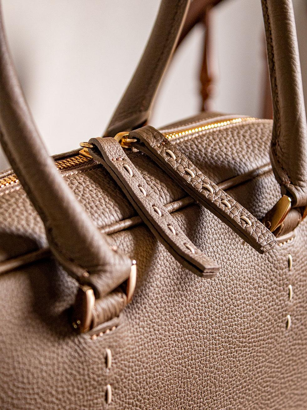 可愛い革紐ステッチが、洗練されたシンプルなデザインにおとなの可愛さをプラス